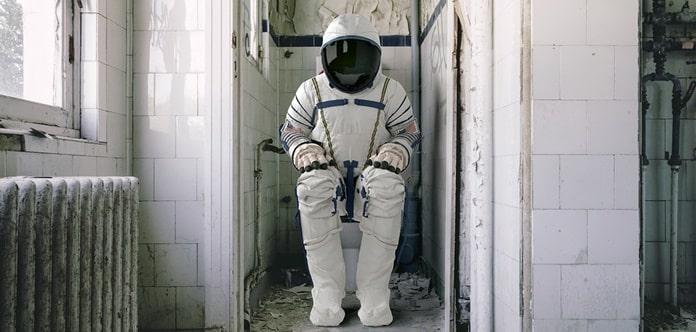 Astronaut in voller Montur auf einer alten Toilette