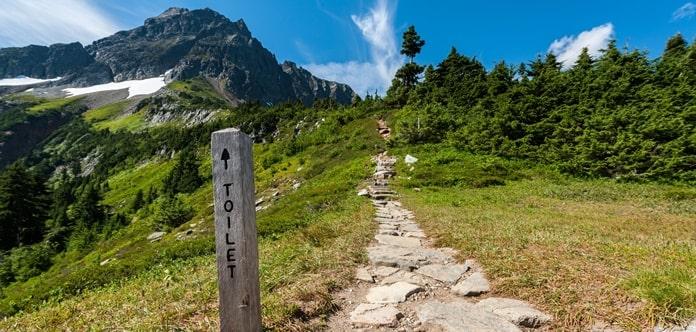 Berglandschaft mit einem Wegweiser, auf dem Toilette steht