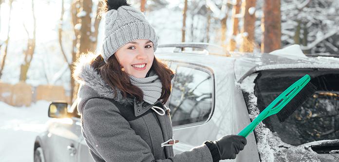 Lächelelnde Frau reinigt ihr Auto