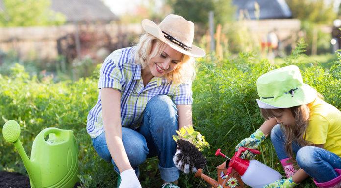 Mutter und Kind bei der Gartenpflege im Sommer